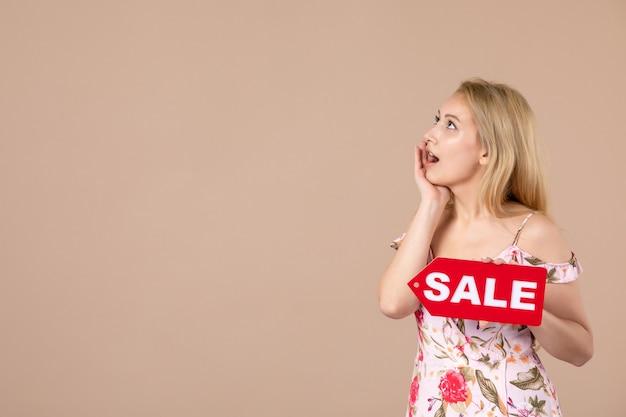 Vooraanzicht van jonge vrouw met rood verkoopbord op bruine muur