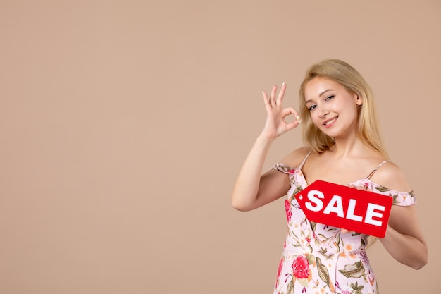 Vooraanzicht van jonge vrouw met rood verkoopbord op lichtbruine muur