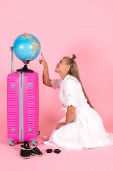 Vooraanzicht van jonge vrouw met roze tas en wereldbol op een roze muur