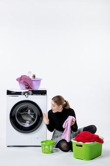 Vooraanzicht van jonge vrouw met wasmachine die vuile kleren op witte muur vouwt