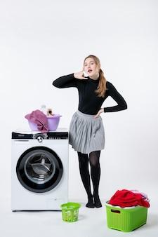 Vooraanzicht van jonge vrouw met wasmachine en vuile kleren op witte muur