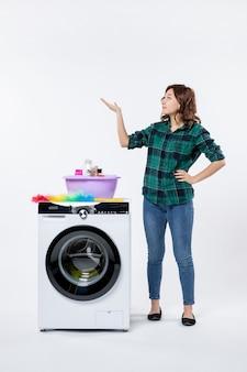 Vooraanzicht van jonge vrouw met wasmachine op witte muur