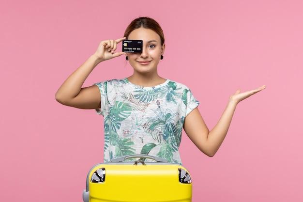 Vooraanzicht van jonge vrouw met zwarte bankkaart op de roze muur