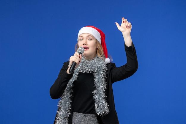 Vooraanzicht van jonge vrouw op nieuwjaarskaraokefeest op de blauwe muur