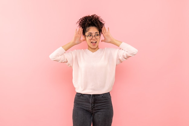 Vooraanzicht van jonge vrouw opgewonden op roze muur