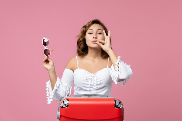 Vooraanzicht van jonge vrouw poseren en voorbereiden op reis met rode tas op lichtroze muur trip