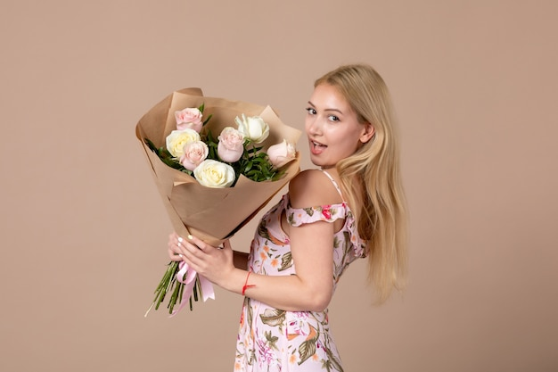 Vooraanzicht van jonge vrouw poseren met boeket van mooie rozen op bruine muur