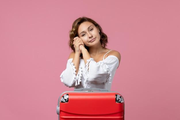 Vooraanzicht van jonge vrouw poseren met rode vakantietas op de roze muur