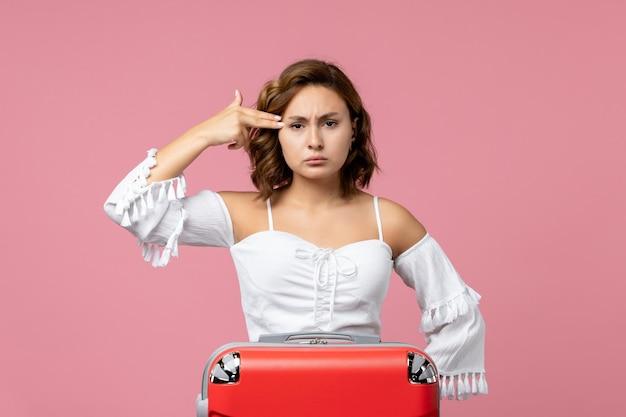Vooraanzicht van jonge vrouw poseren met rode vakantietas op de roze muur Gratis Foto