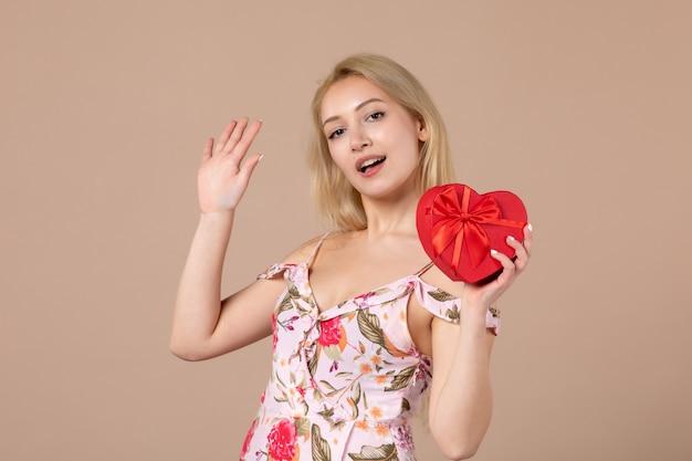 Vooraanzicht van jonge vrouw poseren met rood hartvormig cadeau op bruine muur