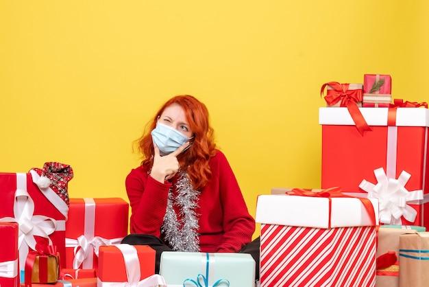 Vooraanzicht van jonge vrouw rond kerstcadeautjes zitten in masker op gele muur