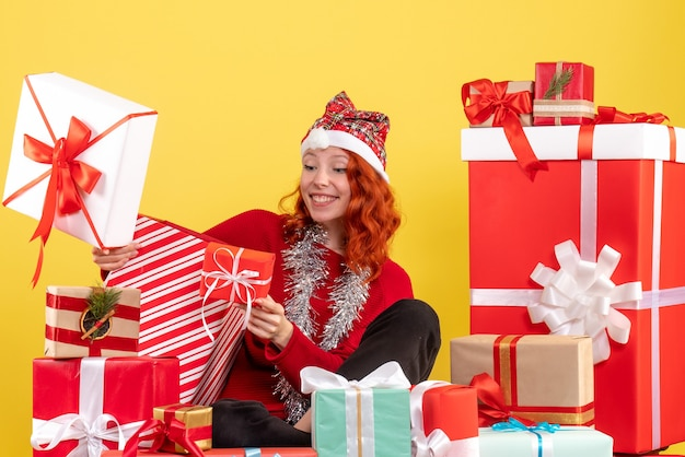 Vooraanzicht van jonge vrouw rond kerstcadeautjes zitten op gele muur