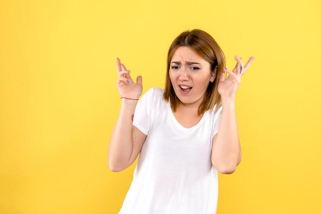Vooraanzicht van jonge vrouw zenuwachtig op gele muur