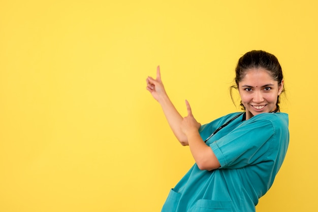 Vooraanzicht van jonge vrouwelijke arts die achter op gele muur richt