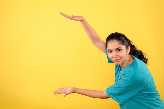 Vooraanzicht van jonge vrouwelijke arts die grootte met handen op gele muur toont