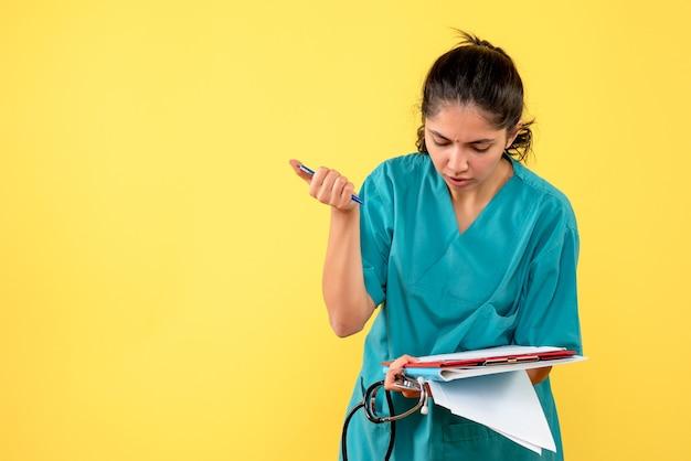 Vooraanzicht van jonge vrouwelijke arts die iets op documenten schrijft die zich op gele muur bevinden