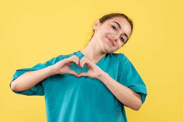 Vooraanzicht van jonge vrouwelijke arts die in medisch overhemd liefde op gele muur verzendt