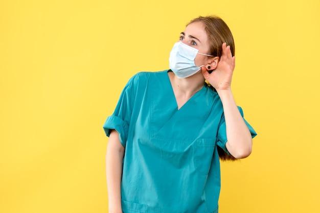 Vooraanzicht van jonge vrouwelijke arts die luistert