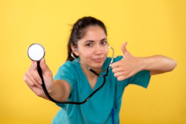 Vooraanzicht van jonge vrouwelijke arts die met een stethoscoop duim maakt ondertekent omhoog op gele muur