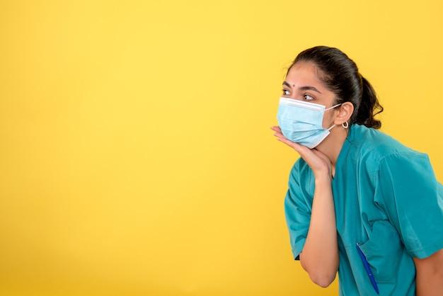 Vooraanzicht van jonge vrouwelijke arts die met medisch masker hand op haar kin op gele muur zet