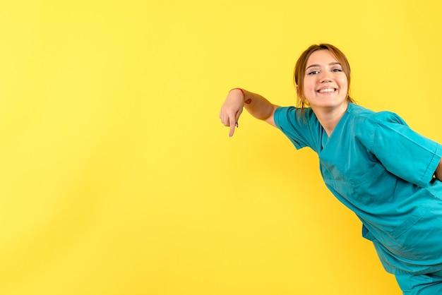 Vooraanzicht van jonge vrouwelijke arts die op gele muur glimlacht