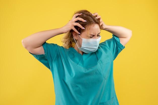 Vooraanzicht van jonge vrouwelijke arts in medisch kostuum en masker op gele muur