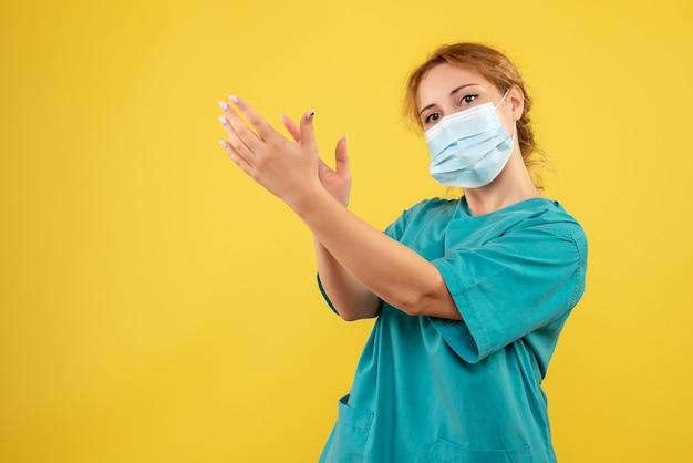 Vooraanzicht van jonge vrouwelijke arts in medisch kostuum en steriel masker dat op gele muur klapt