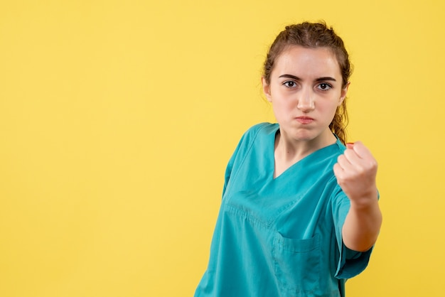 Vooraanzicht van jonge vrouwelijke arts in medisch overhemd boos op gele muur