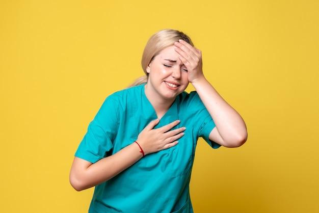 Vooraanzicht van jonge vrouwelijke arts in medisch overhemd die aan hoofdpijn op gele muur lijdt