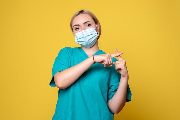 Vooraanzicht van jonge vrouwelijke arts in medisch overhemd en steriel masker op gele muur