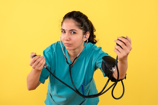 Vooraanzicht van jonge vrouwelijke arts met bloeddrukmeter die haar bloeddruk op gele muur controleert