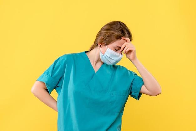 Vooraanzicht van jonge vrouwelijke arts met masker gestrest