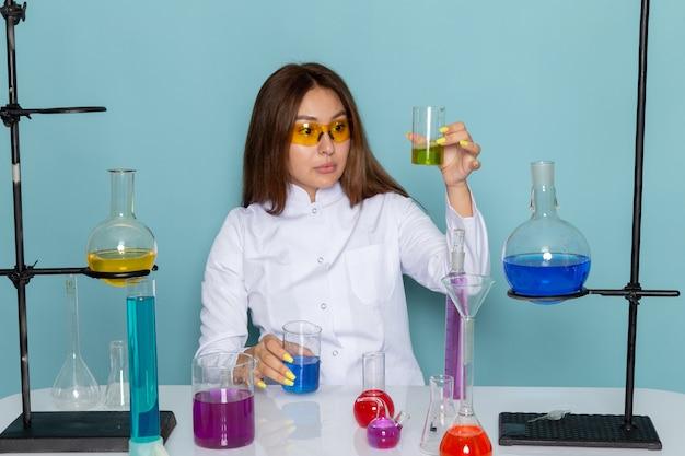 Vooraanzicht van jonge vrouwelijke chemicus in wit pak voor tafel werken met oplossingen
