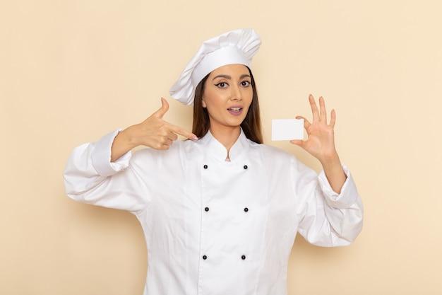 Vooraanzicht van jonge vrouwelijke kok die in wit kokkostuum plastic kaart op lichtwitte muur houdt