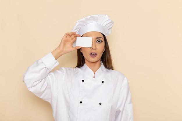 Vooraanzicht van jonge vrouwelijke kok die in wit kokkostuum witte kaart op witte muur houdt