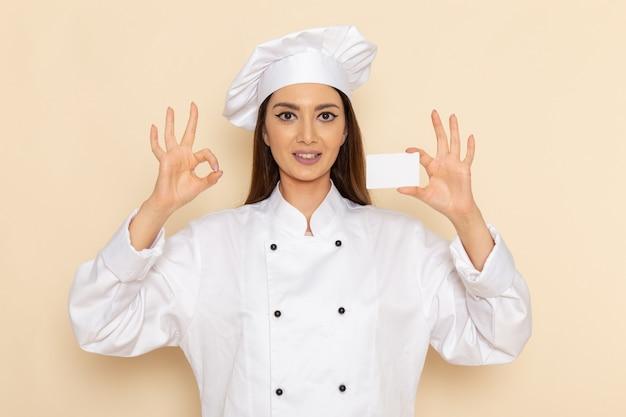 Vooraanzicht van jonge vrouwelijke kok die in wit kokkostuum witte plastic kaart op lichtwitte muur houdt