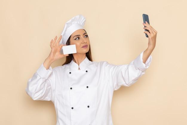 Vooraanzicht van jonge vrouwelijke kok in de holdingskaart van het witte kokkostuum en neemt selfie op lichtwitte muur