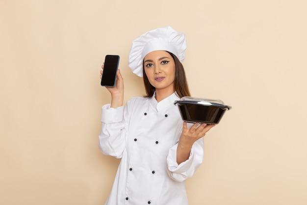 Vooraanzicht van jonge vrouwelijke kok in de witte telefoon van de kokkostuum en zwarte kom op lichtwitte muur