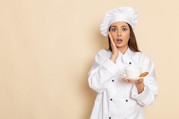 Vooraanzicht van jonge vrouwelijke kok in het witte koekje en de koffie van het kokkostuum op lichtwitte muur