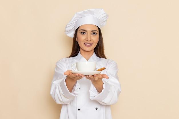 Vooraanzicht van jonge vrouwelijke kok in wit kokkostuum dat koffie op de lichte witte muur houdt