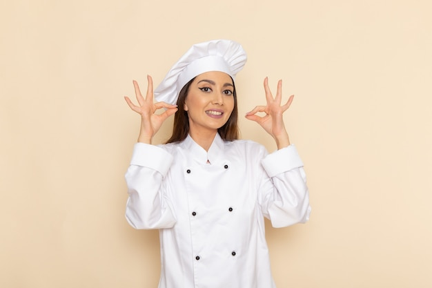 Vooraanzicht van jonge vrouwelijke kok in wit kokkostuum dat op lichtwitte muur glimlacht