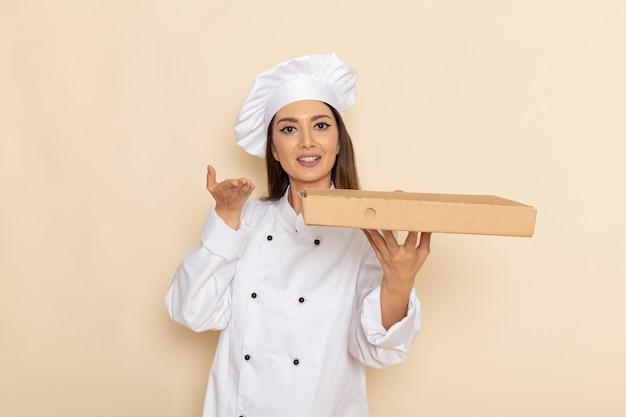 Vooraanzicht van jonge vrouwelijke kok in wit kokkostuum die de doos van de voedsellevering op lichtwitte muur houden