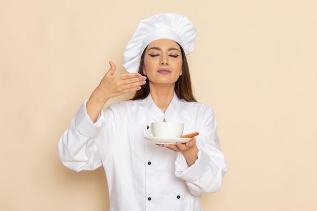 Vooraanzicht van jonge vrouwelijke kok in wit kokkostuum die kop van koffie op de lichtwitte muur houden