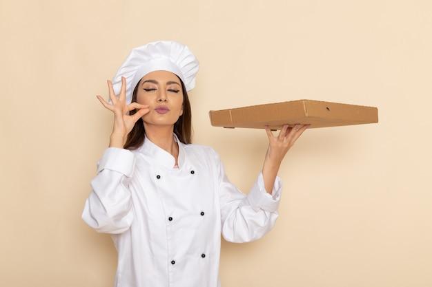 Vooraanzicht van jonge vrouwelijke kok in wit kokkostuum die voedseldoos op de lichtwitte muur houden