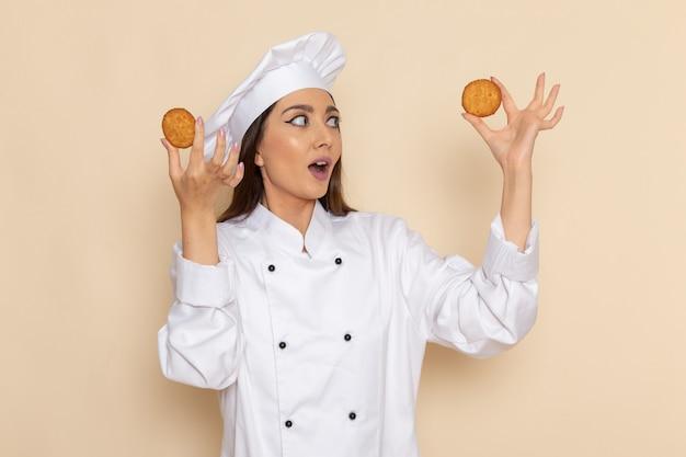 Vooraanzicht van jonge vrouwelijke kok in witte kokkostuum die koekjes op het witte bureau houden het koken voedsel van de het werkkeuken van de keukenbaan