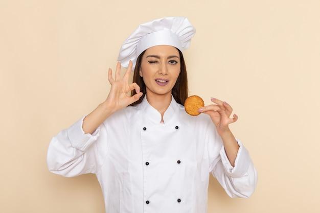 Vooraanzicht van jonge vrouwelijke kok in witte kokkostuum die koekjes op lichte witte muur houden