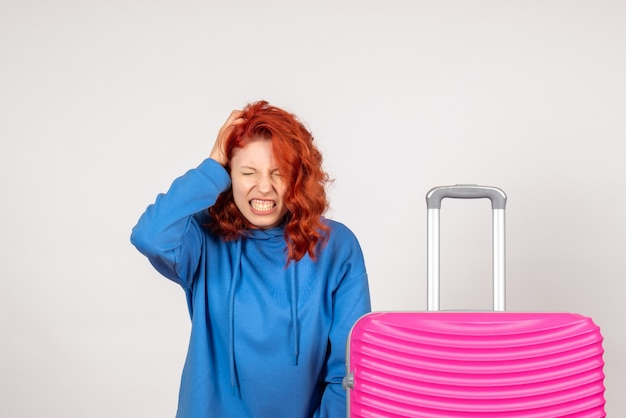 Vooraanzicht van jonge vrouwelijke toerist met roze zak die aan hoofdpijn op witte muur lijdt