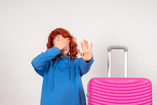 Vooraanzicht van jonge vrouwelijke toerist met roze zak die haar gezicht op witte muur behandelt