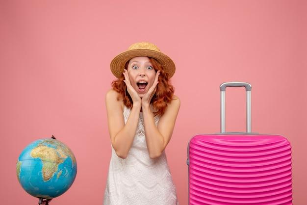 Vooraanzicht van jonge vrouwelijke toerist met roze zak op lichtroze muur