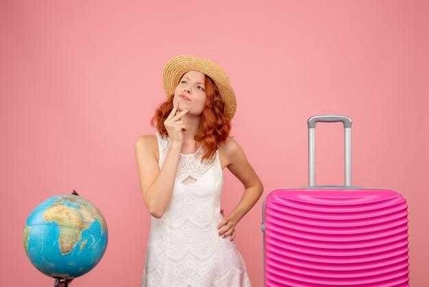 Vooraanzicht van jonge vrouwelijke toerist met roze zak op roze muur